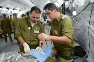 Deux médecins militaires israéliens réalisent une « chirurgie » pendant un exercice d'hôpital de campagne à Beit Naballah, dans le centre d'Israël, le 9 décembre 2013. (Crédit : unité des porte-paroles de l'armée israélienne)